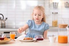 Χαριτωμένη μαρμελάδα διάδοσης μικρών κοριτσιών επάνω στο νόστιμο ψημένο ψωμί Στοκ εικόνα με δικαίωμα ελεύθερης χρήσης