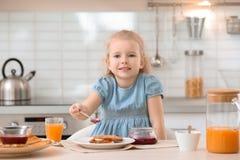 Χαριτωμένη μαρμελάδα διάδοσης μικρών κοριτσιών επάνω στο νόστιμο ψημένο ψωμί Στοκ Φωτογραφία