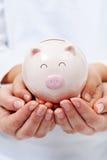 Χαριτωμένη μικρή piggy τράπεζα στα χέρια παιδιών Στοκ Εικόνες