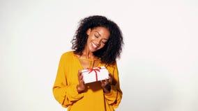 Χαριτωμένη νέα γυναίκα αφροαμερικάνων στο κίτρινο κιβώτιο δώρων εκμετάλλευσης φθινοπώρου τοπ με την κόκκινη κορδέλλα και τόξο στο απόθεμα βίντεο