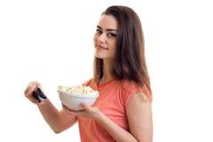 Χαριτωμένη νέα γυναίκα με τη TV μακρινή και pop-corn τους κινηματογράφους προσοχής Στοκ Εικόνες