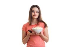 Χαριτωμένη νέα γυναίκα με pop-corn που προσέχει μια TV Στοκ Φωτογραφίες