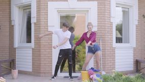 Χαριτωμένη νέα γυναίκα πορτρέτου και όμορφος άνδρας που χορεύουν στο μέρος του σπιτιού Χαρωπό καθαρίζοντας σπίτι ζευγών από κοινο απόθεμα βίντεο