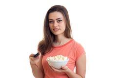 Χαριτωμένη νέα γυναίκα που προσέχει τη TV με pop-corn Στοκ φωτογραφία με δικαίωμα ελεύθερης χρήσης