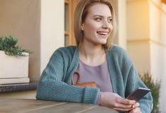 Χαριτωμένη νέα γυναίκα που χρησιμοποιεί το smartphone στην οδό Στοκ φωτογραφία με δικαίωμα ελεύθερης χρήσης