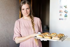 Χαριτωμένη νέα γυναίκα σε ένα ρόδινο φόρεμα με ένα δρεπάνι στην κουζίνα κοντά στο ψυγείο η κυρία στην κουζίνα της Μια νοικοκυρά στοκ εικόνα