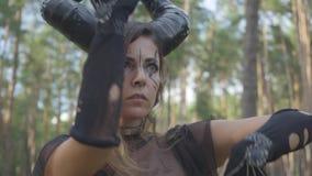 Χαριτωμένη νέα γυναίκα στα θεατρικά κοστούμια του διαβόλου ή επιβλαβής χορός στο δάσος που παρουσιάζει απόδοση ή που κάνει τελετο απόθεμα βίντεο