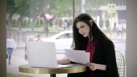 Χαριτωμένη νέα κυρία που εργάζεται στο καθιερώνον τη μόδα επιχειρησιακό κοστούμι επιτραπέζιων καφετεριών Όμορφο πρόσωπο με τη συγ φιλμ μικρού μήκους