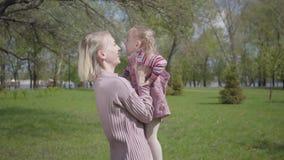 Χαριτωμένη νέα μητέρα πορτρέτου που περιστρέφει την κόρη σε ετοιμότητα στη φύση την ημέρα άνοιξη Παιχνίδι γυναικών και παιδιών στ απόθεμα βίντεο