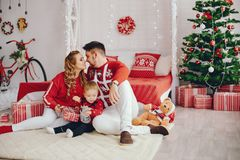 Χαριτωμένη νέα οικογενειακή συνεδρίαση στο σπίτι σε ένα κρεβάτι στοκ εικόνες