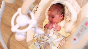 Χαριτωμένη νεογέννητη συνεδρίαση μωρών σε μια ταλάντευση το μωρό λικνίζεται στον ύπνο άσπρη ταλάντευση μωρών απόθεμα βίντεο