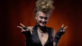 Χαριτωμένη ξανθή γυναίκα στη μαύρη φανέλλα, που χαμογελά και που παρουσιάζει σημάδι ειρήνης με δύο χέρια απόθεμα βίντεο