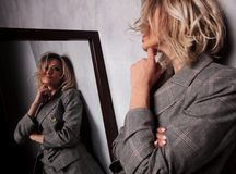 Χαριτωμένη ξανθή γυναίκα στο γκρίζο σακάκι που κοιτάζει στον καθρέφτη στοκ εικόνες