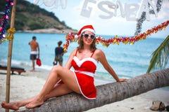 Χαριτωμένη ξανθή γυναίκα στο κόκκινα φόρεμα, τα γυαλιά ηλίου και τη συνεδρίαση καπέλων santa στο φοίνικα στην εξωτική τροπική παρ Στοκ φωτογραφία με δικαίωμα ελεύθερης χρήσης