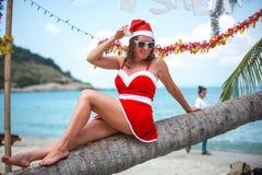 Χαριτωμένη ξανθή γυναίκα στο κόκκινα φόρεμα, τα γυαλιά ηλίου και τη συνεδρίαση καπέλων santa στο φοίνικα στην εξωτική τροπική παρ Στοκ εικόνες με δικαίωμα ελεύθερης χρήσης