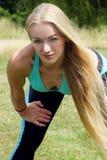Χαριτωμένη ξανθή χαλάρωση γυναικών μετά από να κάνει ένα workout στο πάρκο Στοκ φωτογραφία με δικαίωμα ελεύθερης χρήσης