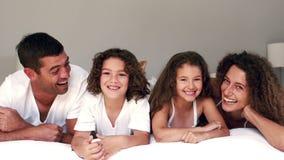 Χαριτωμένη οικογένεια που γελά στο κρεβάτι τους φιλμ μικρού μήκους