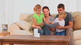 Χαριτωμένη οικογένεια που διαβάζει ένα βιβλίο απόθεμα βίντεο