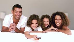 Χαριτωμένη οικογένεια που προσέχει τη TV και που αλλάζει τα κανάλια που βρίσκονται στο κρεβάτι τους απόθεμα βίντεο