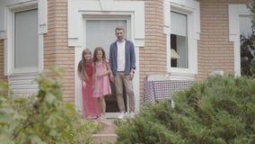 Χαριτωμένη οικογένεια που στέκεται στο μέρος από κοινού Φίλημα μητέρων και πατέρων αντίο σε λίγη κόρη και αυτή που αφήνει το σπίτ απόθεμα βίντεο