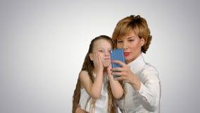 Χαριτωμένη οικογενειακή μητέρα με την κόρη παιδιών που παίρνει selfie την έξυπνη τηλεφωνική φωτογραφία στο άσπρο υπόβαθρο Στοκ Εικόνες
