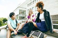Χαριτωμένη ομάδα teenages στην οικοδόμηση του πανεπιστημίου με τα αγκαλιάσματα βιβλίων, τρόπος ζωής σπουδαστών εθνών ποικιλομορφί στοκ εικόνες