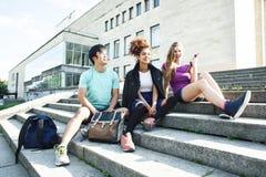 Χαριτωμένη ομάδα teenages στην οικοδόμηση του πανεπιστημίου με τα αγκαλιάσματα βιβλίων, πραγματικός τρόπος ζωής σπουδαστών εθνών  στοκ εικόνες
