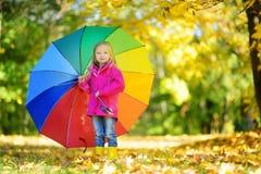 Χαριτωμένη ομπρέλα ουράνιων τόξων εκμετάλλευσης μικρών κοριτσιών την όμορφη ημέρα φθινοπώρου Ευτυχές παιχνίδι παιδιών στο πάρκο φ Στοκ Εικόνα