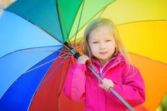 Χαριτωμένη ομπρέλα ουράνιων τόξων εκμετάλλευσης μικρών κοριτσιών την όμορφη ημέρα φθινοπώρου Ευτυχές παιχνίδι παιδιών στο πάρκο φ Στοκ Εικόνες
