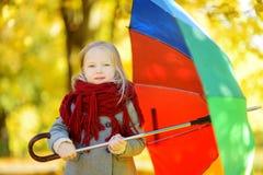 Χαριτωμένη ομπρέλα ουράνιων τόξων εκμετάλλευσης μικρών κοριτσιών την όμορφη ημέρα φθινοπώρου Ευτυχές παιχνίδι παιδιών στο πάρκο φ Στοκ Φωτογραφίες