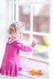 Χαριτωμένη προσοχή κοριτσιών μικρών παιδιών έξω ενός παραθύρου Στοκ φωτογραφία με δικαίωμα ελεύθερης χρήσης