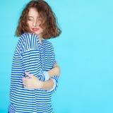 χαριτωμένη σγουρή γυναίκα στα περιστασιακά ενδύματα στο μπλε Στοκ Φωτογραφία