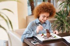 Χαριτωμένη σγουρή νέα γυναίκα που τρώει το επιδόρπιο στον καφέ Στοκ εικόνες με δικαίωμα ελεύθερης χρήσης