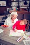 Χαριτωμένη σκοτεινός-μαλλιαρή εγγονή που στέλνει το χρόνο με την αγαπώντας γιαγιά της στοκ εικόνες