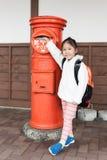 Χαριτωμένη σταλμένη τουρίστας επιστολή κοριτσιών στο ταχυδρομικό κουτί Στοκ εικόνες με δικαίωμα ελεύθερης χρήσης