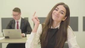 Χαριτωμένη στοχαστική νέα γυναίκα πορτρέτου στην επίσημη συνεδρίαση ένδυσης στο πρώτο πλάνο στο γραφείο ενώ ο άνδρας συνάδελφός τ απόθεμα βίντεο