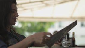 Χαριτωμένη συμπαθητική γυναίκα που φαίνεται επιλογές στο εστιατόριο και που διορθώνει την τρίχα της Μόνο κορίτσι που στηρίζεται σ φιλμ μικρού μήκους