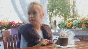 Χαριτωμένη συνεδρίαση έφηβη στον καφέ, χαμογελώντας, χαλαρώνοντας και για να πιει το τσάι φιλμ μικρού μήκους