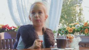 Χαριτωμένη συνεδρίαση έφηβη στον καφέ, χαμογελώντας, χαλαρώνοντας και για να πιει το τσάι απόθεμα βίντεο