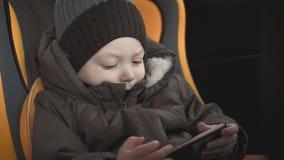 Χαριτωμένη συνεδρίαση αγοράκι μικρών παιδιών στο κάθισμα αυτοκινήτων και προσοχή ενός βίντεο από το έξυπνος-τηλέφωνο Παιχνίδι παι φιλμ μικρού μήκους
