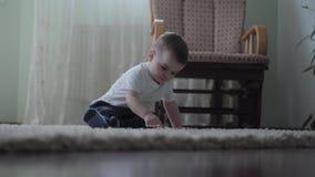Χαριτωμένη συνεδρίαση αγοράκι στο πάτωμα στο χνουδωτό τάπητα που παίζει μόνο ενώ η νέα μητέρα του που περπατά στο πρώτο πλάνο μέσ απόθεμα βίντεο