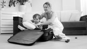 Χαριτωμένη συνεδρίαση αγοριών μικρών παιδιών χαμόγελου στη βαλίτσα ενώ πράγματα συσκευασίας μητέρων για το ταξίδι Στοκ Εικόνα