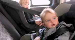 Χαριτωμένη συνεδρίαση κοριτσιών και αγοριών στη πίσω θέση αυτοκινήτων απόθεμα βίντεο