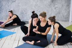 Χαριτωμένη συνεδρίαση κοριτσιών και κοινωνικοποίηση με την ομάδα μετά από την κατηγορία γιόγκας τους στοκ εικόνα με δικαίωμα ελεύθερης χρήσης
