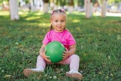 Χαριτωμένη συνεδρίαση κοριτσάκι παιδιών στη χλόη στο πάρκο, που παίζει με την πράσινη σφαίρα και που χαμογελά Στοκ φωτογραφίες με δικαίωμα ελεύθερης χρήσης