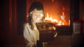 Χαριτωμένη συνεδρίαση κοριτσιών στο σκοτεινό καθιστικό στο κάψιμο της εστίας και το άνοιγμα του κιβωτίου με το χριστουγεννιάτικο  απόθεμα βίντεο