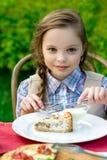 Χαριτωμένη συνεδρίαση μικρών κοριτσιών από τον πίνακα γευμάτων και κατανάλωση Στοκ Φωτογραφίες
