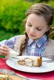 Χαριτωμένη συνεδρίαση μικρών κοριτσιών από τον πίνακα γευμάτων και κατανάλωση Στοκ Εικόνα
