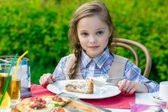 Χαριτωμένη συνεδρίαση μικρών κοριτσιών από τον πίνακα γευμάτων και κατανάλωση Στοκ Εικόνες