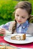 Χαριτωμένη συνεδρίαση μικρών κοριτσιών από τον πίνακα γευμάτων και κατανάλωση Στοκ φωτογραφία με δικαίωμα ελεύθερης χρήσης